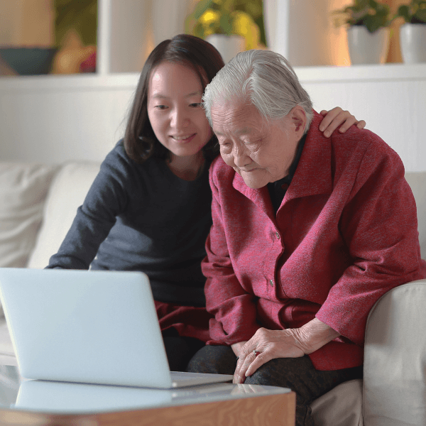 A woman shows her grandmother a website on a laptop